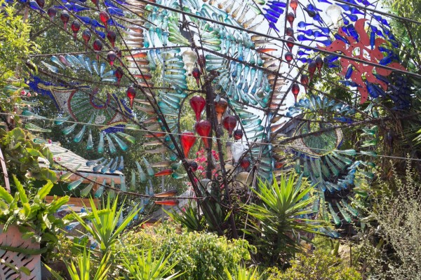 Phantasma Gloria in Los Angeles, California featuring colored bottles on rebar with greenery surrounding.