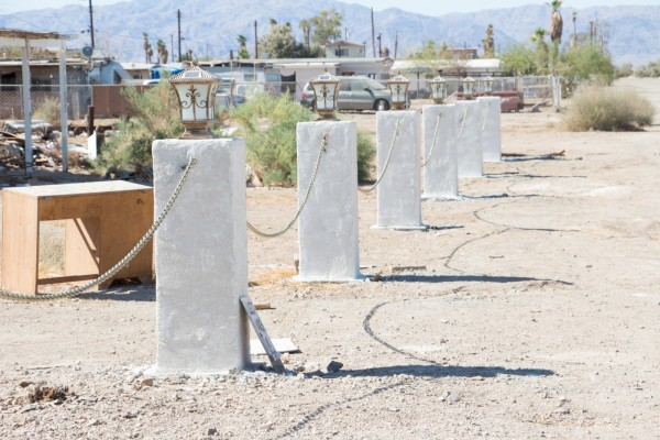 Six concrete pillars with chains connecting them in a desert landscape.